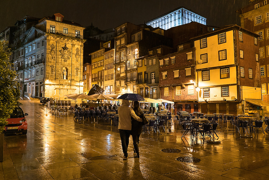 Lovers walk in the rain near the Rio Douro in Oporto, Portugal.
