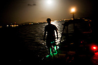 ST. CROIX - AUG 15: Chris Niebuhr, a member of the National Park Service turtle research team of volunteers, steps off the boat and onto Buck Island (a federally protected island and turtle nesting ground) in St. Croix, U.S. Virgin Islands, to begin a long night of sea turtle research under a full moon on August 15, 2008. The lights in the background are of St. Croix. Turtle researchers like Chris spend a few months during each nesting season (when the female sea turtles lay their eggs) monitoring and caring from this endangered species.  (Photo by Landon Nordeman)
