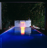 A raised tile wall at the far end of the outdoor swimming pool has a waterfall which is illuminated by fibre optics at night