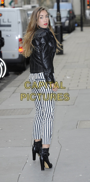 Harley Moon Kemp .The daughter of Martin Kemp & Shirlie Holliman at a photocall for the Autumn/Winter collection of the Italian fashion house Stefanel, Westbury Hotel, London, England..March 19th, 2013.full length black leather jacket white striped stripes trousers ankle boots back behind rear looking over shoulder .CAP/DH.©David Hitchens/Capital Pictures.