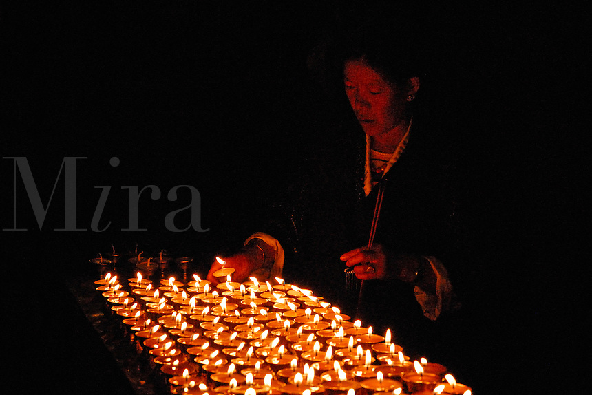 Buddhist pilgrim lights a yak butter lamp to eliminate darkness and enlighten the mind, at Sera Monastery, Lhasa, Tibet, China.