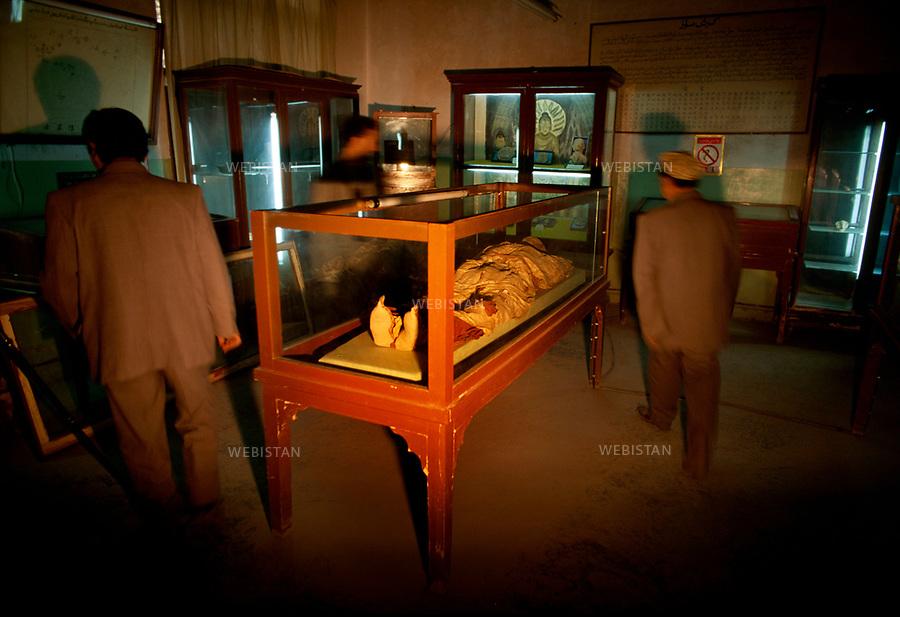 Musee de Khotan. Visiteurs dans une salle d'archéologie et d'éthnologie du musée de Khotan. Une momie dans une cage de verre au milieu de visiteurs est exposée au Musée de Khotan. Les momies sont remarquablement bien conservées dans le sable et le sel de la terre de la region. Khotan Museum. A mummy in a glass cage in the middle of the passers-by exposed in the Khotan Museum. The mummies are remarkably well conserved in the sand and the salty earth of the region.
