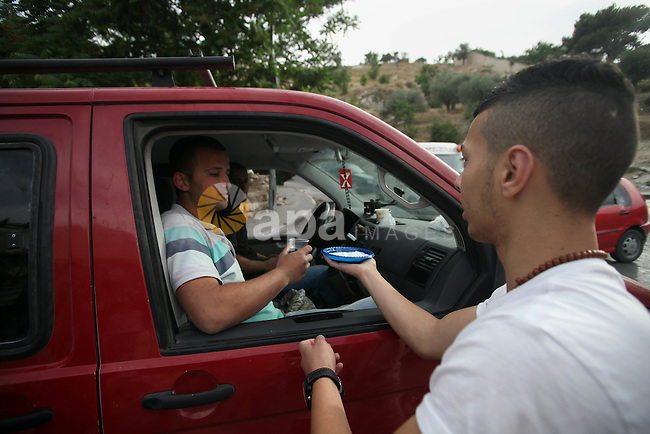A Palestinian youth distributes water and salt during a protest to solidarity with Palestinian prisoners, in the East Jerusalem neighborhood of Silwan on May 29, 2014. It was about 120 Palestinians imprisoned without trial in Israel on an open hunger strike, and only salt intake, drinking water, for the past 30 days to demand an end to so-called 'administrative detention. Photo by Saeed Qaq