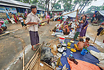 A Rohingya man who recently crossed the border from Myanmar disassembles his family's temporary shelter as they complete registration in the Kutupalong Refugee Camp near Cox's Bazar, Bangladesh. More than 600,000 Rohingya refugees have fled government-sanctioned violence in Myanmar for safety in this and other camps in Bangladesh.