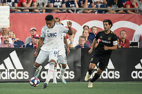 FOXBOROUGH, MA - AUGUST 3: Juan Agudelo #17 of New England Revolution passes the ball forward with Carlos Vela #10 of Los Angeles FC in pursuit during a game between Los Angeles FC and New England Revolution at Gillette Stadium on August 3, 2019 in Foxborough, Massachusetts.