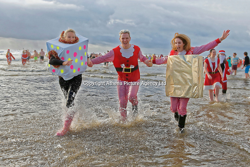 Pictured: A man dressed as Santa and two women dressed as gifts splash about in the water. Tuesday 26 December 2017<br /> Re: Hundreds took part in this year's Boxing Day Walrus Dip which see people in fancy dress taking to the sea at Cefn Sidan beach in Pembrey Country Park, west Wales, UK.