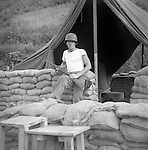 A United States Soldier of the Second Infantry Division holds a rifle while standing next to a heavily fortified, with sand bags, tent at the units command post during the Korean War. These are photos of the 2nd Infantry Division during the Korean War in 1950 or 1951.