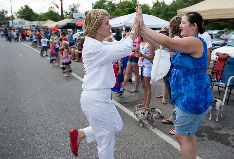 """UNITED STATES - JULY 4: U.S. Senate candidate Rep. Shelley Moore-Capito, R-W.Va., gets high-fives from the crowd as she walks in the Ripley 4th of July Parade in Ripley, W. Va., on July 4, 2014. The parade is billed as """"the USA's largest small town Independence Day Celebration. (Photo By Bill Clark/CQ Roll Call)"""