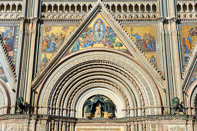 Close up of the main door with mosaics depicting the the Virgin Mary created between 1350 and 1390 after designs by artist Cesare Nebbia and sculpture of the Madonna and Child created by Andrea Pisano in 1347  on the14th century Tuscan Gothic style facade of the Cathedral of Orvieto, designed by Maitani, Umbria, Italy