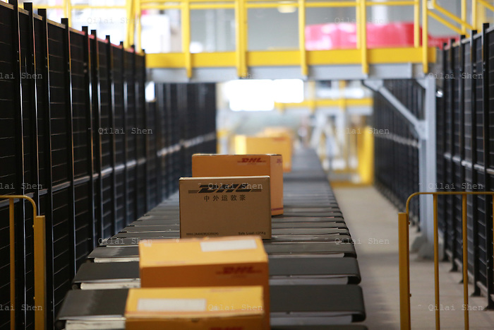 Packages move down a coveyor line at the newly opened Deutsche Post DHL North Asia Hub in Shanghai, China on 12 July 2012. DHL is expecting its business to grow in Asia as the slowing economy will force its customers to reduce inventory and depend more on logistics companies to move parts and products.
