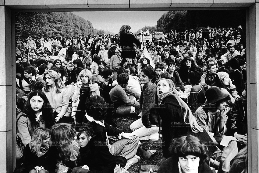 France. Ile-de-france Department. Paris. Two seat and talk together below a giant phgotography celebrating a women's march and demonstration. A demonstration or street protest is action by a mass group or collection of groups of people in favor of a political or other cause; it normally consists of walking in a mass march formation and either beginning with or meeting at a designated endpoint, or rally, to hear speakers. Actions such as blockades and sit-ins may also be referred to as demonstrations. 6.11.10 © 2010 Didier Ruef