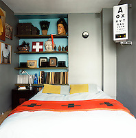 A snug bedroom accommodates a double bed and shelving built into a recess