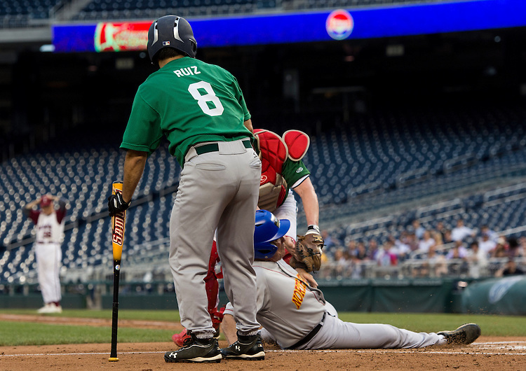 UNITED STATES - JUNE 25: Rep. Raul Ruiz, D-Calif., block the view of a play at homeplate during the Roll Call Congressional Baseball Game on Wednesday, June 25, 2014. (Photo By Bill Clark/CQ Roll Call)