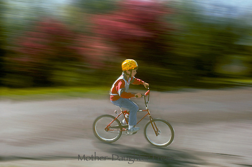 Kid rides red bicycle
