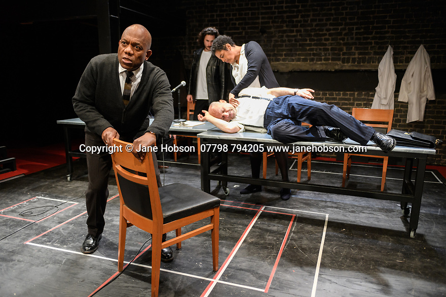 "London, UK. 10.04.2017. A brand new adaptation of Albert Camus' ""The Plague"" opens at the Arcola Theatre. Adapted and directed by Neil Bartlett. Picture shows: Burt Caesar (Grand),  Billy Postlethwaite (Mr Rambert), Joe Alessi (Mr Cottard), Sara Powell (Dr Rieux). Photograph © Jane Hobson."