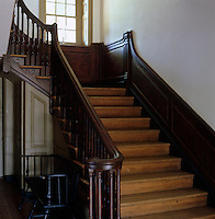 A panelled wooden staircase leads up to the first floor