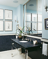 The stylish bathroom is decorated in a soft pale blue, which perfectly sets off the dark blue grey tiling and washstand.