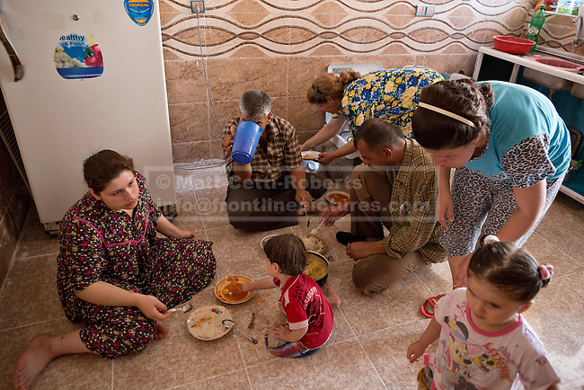 Christian refugee Ra'id Samir Kamal, 45 (R kneeling), formerly a driver in Mosul, eats lunch with some of the members of his extended family in the partially built house they inhabit in Hamdaniyah, Iraq.