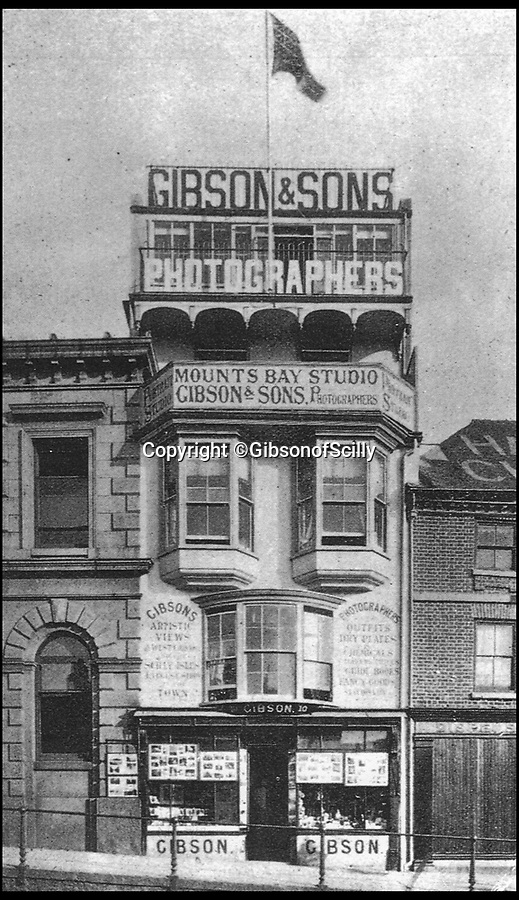 BNPS.co.uk (01202 558833)<br /> Pic: GibsonOfScilly/BNPS<br /> <br /> Gibson & Son's premises in Penzance.<br /> <br /> An archive of eye-opening photographs documenting the grim reality of Poldark's Cornwall has emerged for sale for £25,000.<br /> <br /> More than 1,500 black and white images show the gritty lives lived by poverty-stricken families in late 19th and early 20th century Cornwall - around the same time that Winston Graham's famous Poldark novels were set.<br /> <br /> The collection reveals the lowly beginnings of towns like Rock, Fowey, Newquay and St Ives long before they became picture-postcard tourist hotspots.<br /> <br /> Images show young filth-covered children playing barefoot in squalid streets, impoverished families standing around outside the local tax office, and weather-beaten fishwives tending to the day's catch.<br /> <br /> The Cornish archive, comprising 1,200 original photographic prints and 300 glass negative plates, is tipped to fetch £25,000 when it goes under the hammer as one lot at Penzance Auction House.