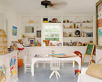 In the children's playroom toys and games are stored on open shelves with built-in cupboards for more storage and the floor is covered in practical grey linoleum