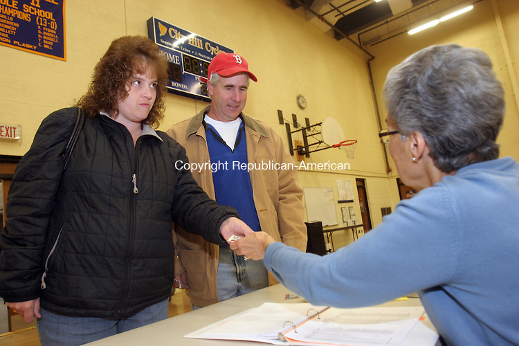 NAUGATUCK, CT-06 November 2013-110513TK04-  Voters at City Hill Middle School in Naugatuck,  Maria and Charles Olegi are checked in before voting in by voting checker Mary Oliverira. Tom Kabelka Republican-American