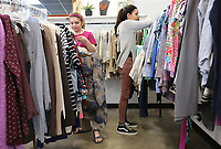 NWA Democrat-Gazette/DAVID GOTTSCHALK Hannah Beck(from left), 14, a volunteer with Arkanserve a volunteer group from New Heights Church, and Elizabeth Razo, 10, a volunteer, hang sorted clothes Tuesday, March 19, 2019, at the new location of Beautiful Lives Thrift Boutique at 245 East Township Street in Fayetteville. The non profit, that supports five organizations for women and children in crisis. The boutique is also the new location of The Global Shoppe that offers handmade products made by women to enhance the lives of women.