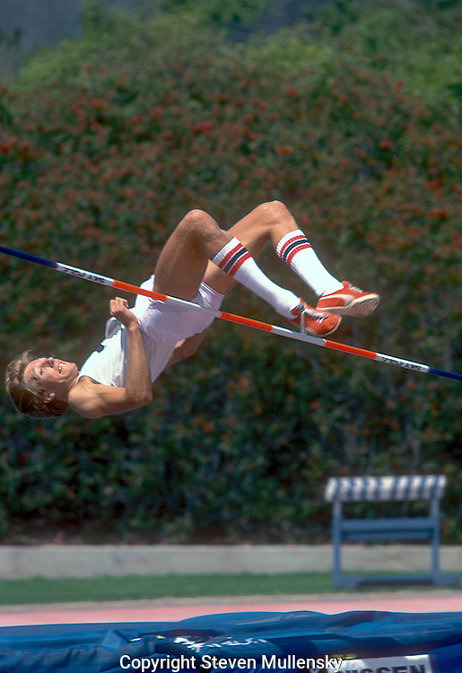 "High Jumper Dwight Stones clears the bar during the 1978 AAU Track and Field Championships at Drake Stadium at UCLA..Dwight Edwin Stones (born December 6, 1953 in Los Angeles, California) is an American television commentator and a two-time Olympic bronze medalist and former three-time world record holder in the men's high jump. During his 16-year career, he won 19 national championships. In 1984, Stones became the first athlete to both compete and announce at the same Olympics. Since then, he has been a color analyst for all three major networks in the United States and continues to cover track and field on television...Stones set his first world record when he cleared 2.30 m (7 ft 6+1?2 in) in 1973 at Munich, Germany. That jump also made him the first ""flop"" jumper to set a world high jump record, five years after Dick Fosbury made that jumping style famous while winning the Mexico City Olympics. Stones raised the world record to 2.31 m (7 ft 7 in) in 1976 and added another centimeter to the record two months later...Stones was one of the world's top high jumpers from 1972 to 1984 and has been twice named the World Indoor Athlete of the Year by Track & Field News. At age 18, he represented the U.S. for the first time at the 1972 Olympic Games, placing third in the high jump competition. Four years later, he was again third. He returned to the Olympics in 1984, finishing fourth after setting his 13th American record at that year's Trials...Stones attended California State University, Long Beach and is a member of that University's Hall of Fame...In 1988, Stones was inducted into the USA Track and Field Hall of Fame."