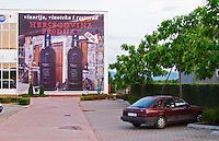 Advertising poster billboard on the outside of the winery. Car in the parking lot. Hercegovina Produkt winery, Citluk, near Mostar. Federation Bosne i Hercegovine. Bosnia Herzegovina, Europe.