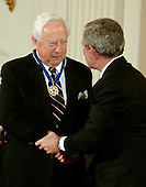 "Washington, D.C. - December 15, 2006 -- David McCullough receives the Presidential Medal of Freedom  from United States President George W. Bush and first lady Laura Bush during a ceremony in the East Room of the White House on Friday, December 15, 2006.  The medal is the nation's highest civil award.  It may be awarded ""to any person who has made an especially meritorious contribution to (1) the security or national interests of the United States, or, (2) world peace, or (3) cultural or other significant public or private endeavors"".  One of our Nation's most distinguished and honored historians, David McCullough has taken his own place in American history.  His books have earned him the respect of general audiences and scholars alike and have received numerous awards, including two National Book Awards and two Pulitzer Prizes.  The author of rigorous works on Harry Truman, John Adams, and the young Theodore Roosevelt, he is one of our foremost authorities on the American Presidency.  The United States honors David McCullough for his lifelong efforts to document the people, places, and events that have shaped America.<br /> Credit: Ron Sachs / CNP"