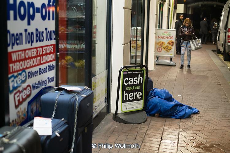 Man sleeping on damp pavement, Charing Cross, London.