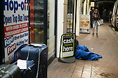 Man sleeping on damp pavement, Charing Cross, London.
