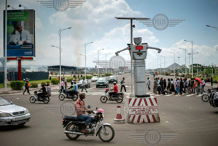 An 8 foot tall humanoid traffic robot equipped with a rotating chest and video cameras controls and monitors traffic on a busy road in Kinshasa. <br /> Built by Women's Tech, a small enterprise started by Therese Kirongozi, a local entrepreneur, the humanoid traffic robots are intended to blend the functions of traffic lights with human traffic police officers to control and monitor traffic flow. They are solar powered, equipped with green and red lights and can play pre-recorded messages to pedestrians to let them know when it's safe to cross the street. They also have in-built video cameras which convey footage back to a central office where it is evaluated and used to enhance traffic flow in the city and to prosecute traffic offences.