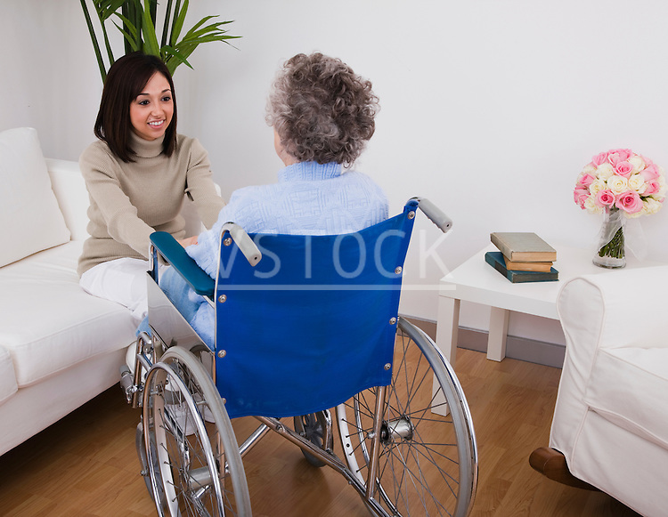 Young woman visiting senior woman in wheelchair