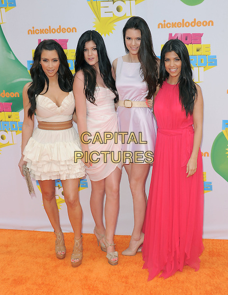 KIM KARDASHIAN, KYLIE JENNER, KENDALL JENNER & KOURTNEY KARDASHIAN.attending The 24th Annual Kids' Choice Awards held at USC's Galen Center in Los Angeles, California, USA, .April 2nd 2011..full length dress cleavage white cream strapless ruffle  beige tan brown belt waistband  clutch bag snakeskin snake sandals  platform sisters family siblings pink long maxi  ruffles tiered .CAP/RKE/DVS.©DVS/RockinExposures/Capital Pictures.