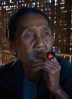 Woman smoking a cheerot (traditional cigar) at Minnanthu Village near Bagan, Myanmar/Burma