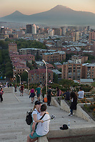 """Armenia. Yerevan. Sunset. Aerial view from Cascade Complex on old and new buildings in the city center.Most of the constructions are dating from Soviet time. A loving couple wth selfie stick is taking pictures on mobile phone. On the horizon, the Ararat Mountain which is a snow-capped and dormant compound volcano in the extreme east of Turkey. It consists of two major volcanic cones: Greater Ararat (R) and Little Ararat (L). Greater Ararat is the highest peak in Turkey and the Armenian Highland with an elevation of 5,137 m; Little Ararat's elevation is 3,896 m. The Ararat massif is about 35 km wide at ground base. The """"mountains of Ararat"""" have been widely accepted in Christianity as the resting place of Noah's Ark, despite contention that Genesis 8:4 does not refer specifically to Mt. Ararat. It is the principal national symbol of Armenia and has been considered a sacred mountain by Armenians. It is featured prominently in Armenian literature and art and is an icon for Armenian irredentism. Yerevan, sometimes spelled Erevan, is the capital and largest city of Armenia. 2.10.2019 © 2019 Didier Ruef"""
