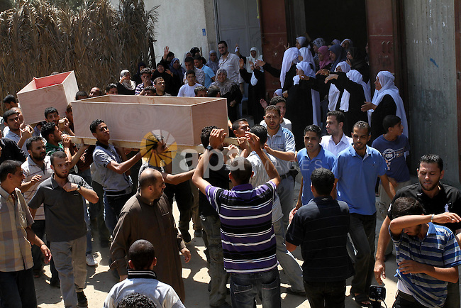 Palestinian mourners carry the coffins of Moataz Qouriqa, a commander of Islamic Jihad's Al-Quds Brigade, and his brother during their funeral in Gaza City on August 20, 2011 after Israeli planes launched air strikes in Gaza in retaliation for suspected Islamist militants killing eight Israelis near the Egyptian border. Photo by Mohammed Asad