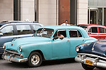 Havana, Cuba; a classic blue 1951 Plymouth car driving down the street in Old Havana