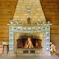Detail of a rustic stone fireplace decorated with coloured tiles against a wood-clad wall
