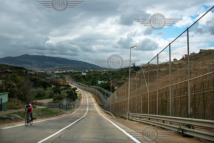 A cyclist rides a road that runs beside the border fence separating the Spanish exclave of Melilla and Morocco. Melilla is a Spanish city on the north coast of Africa, bounded by Morocco and the Mediterranean Sea. Many would-be migrants see it as the gateway to Europe which accounts for the high-level of security along its borders.