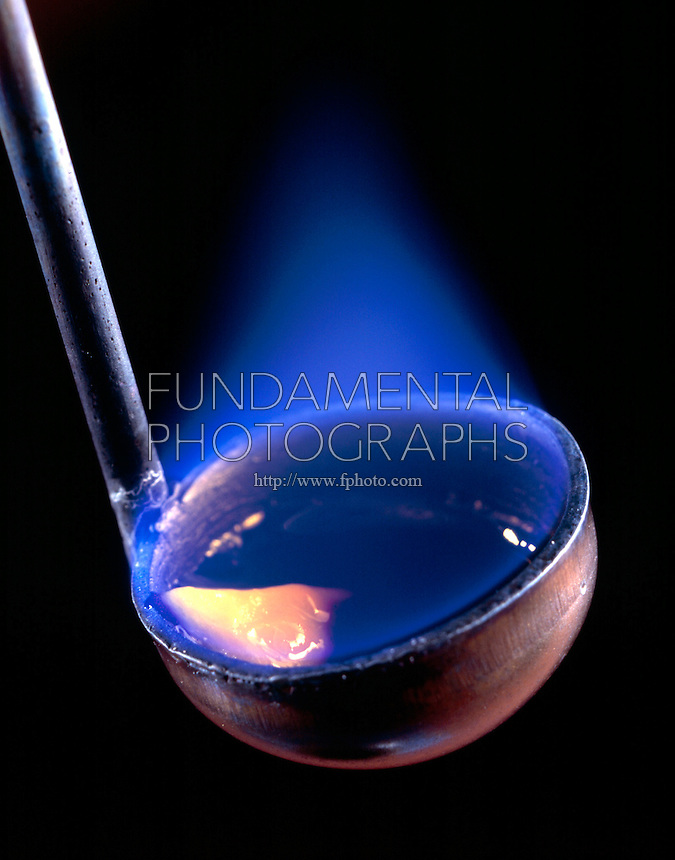 SULFUR BURNING IN AIR<br /> Lump Sulfur In Deflagration Spoon<br /> Orthorhombic lump sulfur ignites in air above 261 degC with a blue flame to form sulfur dioxide gas (SO2).  SO2 is slowly oxidized in the atmosphere to form SO3 which dissolves in rainwater to give sulfuric acid or acid rain.
