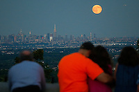 People watch the Blue moon rises next to the Empire State Building and middle Manhattan while it is seen from New Jersey.  07/31/2015. Eduardo MunozAlvarez/VIEWpress