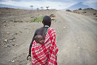 A woman carries a baby on her back along the road between Arusha and Loliondo. The government of Tanzania is planning to turn this dirt track into a highway that will connect isolated communities and bring much needed development to the marginalised Masaai. However, the highway will cut straight through the Serengeti National Park, a World Heritage Site, disrupting animal migration, which would have disastrous consequences for the entire park ecosystem.