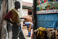Jockey James Muhindi looked out from the gate of  the converted stable that he uses as  his livingquarters as farrier George Njuguna shoes a horse in the yard of trainer Oliver Gray at Ngong Racecourse, Nairobi, Kenya. March 22, 2013. Photo: Brendan Bannon
