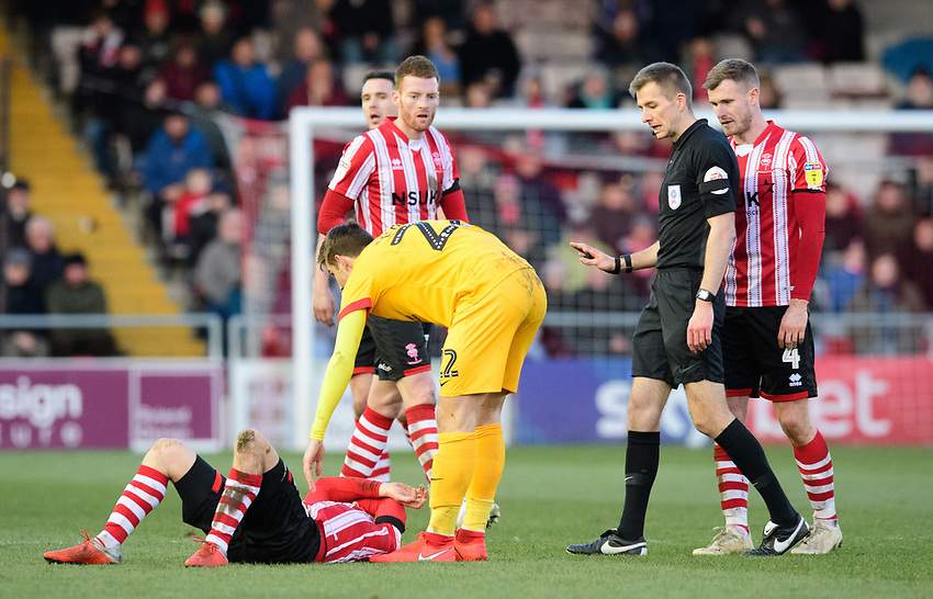Referee Michael Salisbury watches on as Northampton Town's Timi Elsnik checks on Lincoln City's Tom Pett after he had committed a foul<br /> <br /> Photographer Chris Vaughan/CameraSport<br /> <br /> The EFL Sky Bet League Two - Lincoln City v Northampton Town - Saturday 9th February 2019 - Sincil Bank - Lincoln<br /> <br /> World Copyright © 2019 CameraSport. All rights reserved. 43 Linden Ave. Countesthorpe. Leicester. England. LE8 5PG - Tel: +44 (0) 116 277 4147 - admin@camerasport.com - www.camerasport.com