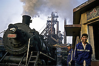 A steam train passes through two steel workers in Benxi Iron and Steel Group in Liaoning. China's second-largest steelmaker Anshan Iron & Steel Group has merged with smaller rival Benxi Steel Group to create a company with capacity that will match the mainland's biggest steelmaker, Shanghai Baosteel Group..01 Sep 2005