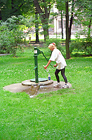 Woman age 21 pumping water in city park.  Krakow Poland