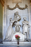 "Picture and image of the late borgeoise realistic style stone sculpture of the Gallino tomb sculpted by  G. Moreno 1894.  In the tomb, the bust that portrays the deceased Carolina receives the kiss of a child, probably the niece, supported by a young woman - the mother, or perhaps the elder sister - whose face is marked by pain; on the right an older man, presumably her husband, stands aside, almost absent, looking down at the ground. The most intimate tones and psychological introspection are grafted here in the language of bourgeois Realism: with undoubted technical virtuosity Moreno offers a rigorous ""quantitative"" description of reality, dwelling on every single detail of faces, clothing, accessories and hairstyles . Section A, no 54, The monumental tombs of the Staglieno Monumental Cemetery, Genoa, Italy"