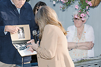 A man displays a picture of Lee Harvey Oswald and explains a JFK conspiracy theory to Democratic presidential candidate and spiritual guru Marianne Williamson during the q&a period after the candidate spoke to a small crowd in the back yard of Kathleen O'Donnell at a campaign house party event in Keene, New Hampshire, on Wed., May 22, 2019.