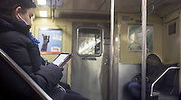 A woman reads on a tablet computer during her subway ride in New York on Saturday, January 26, 2013. (© Richard B. Levine)